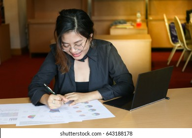 working woman in black dress look happy to see charts paper on wooden desk