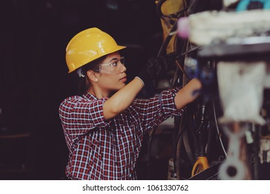 working woman concept : Young Asian girl working with machine in industrial