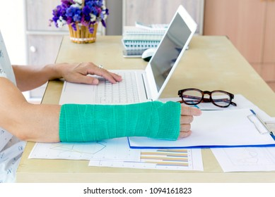 working woman with green cast on arm working on laptop in office, focus on broken hand.