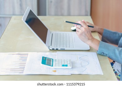working woman holding pencil working with laptop, calculator and report data on wood desk in office.