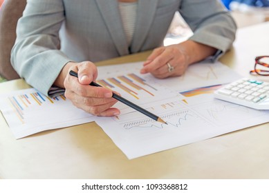 working woman with laptop, calculator, eyeglasses and report data on wood desk in office