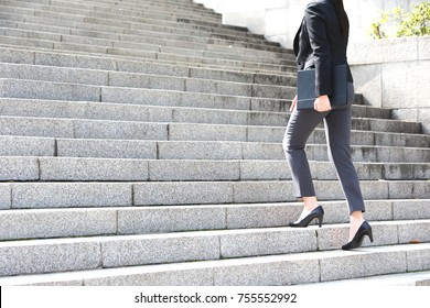 a working woman walking up the stairs
