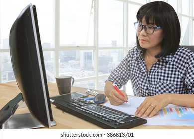 working woman work on office computer and writing paper report