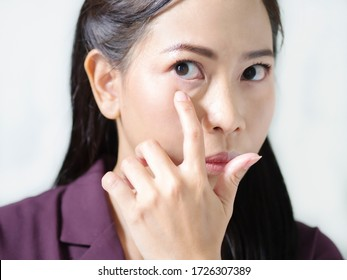Working women has eyes inflammation with iris infection due to macular degeneration from mobile phone and computer. Vitreous and eye floaters. Aged wrinkle eyes. Isolated white background.
