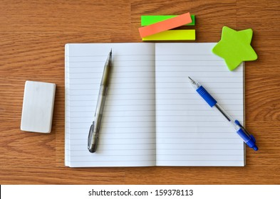 Working wooden desk with eraser, pencil, pen and sticky note