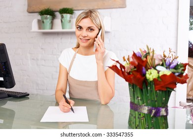 Working for you. Portrait of appealing professional florist talking on mobile phone and expressing positivity while standing at the counter
