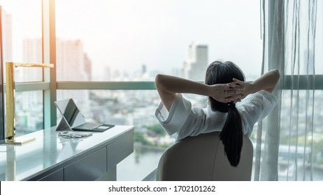 Work-life quality balance concept with happy city lifestyle Asian girl having a good day waking up from sleep in morning taking some rest, lazily relaxing in comfort home condominium or hotel bed room