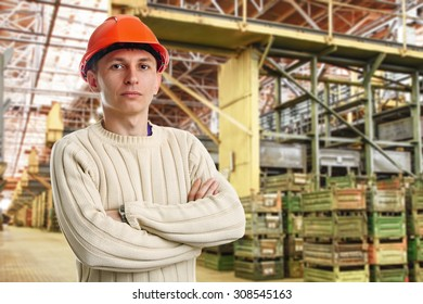 Workman in big storage room with metal boxes in factory