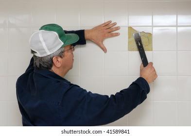 Workman breaking up bathroom tiles