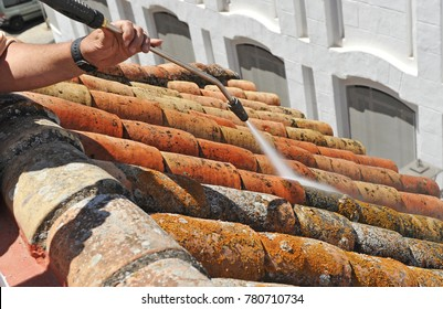 A workman cleaning a tiles roof with high pressure water