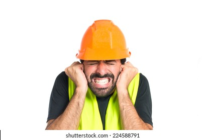 Workman covering his ears over white background