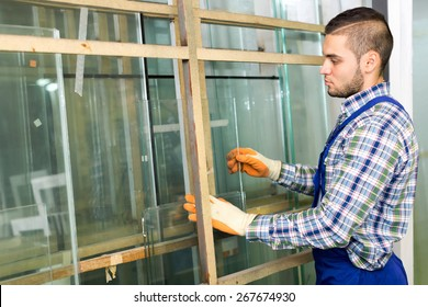 Workman cutting glass for windows at workshop