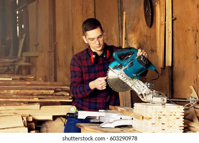 Workman dressed in the checkered shirt checking the circular saw at the sawmill. Timbers on background.