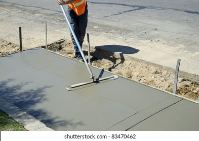 Workman finishes and smooths concrete surface on new sidewalk