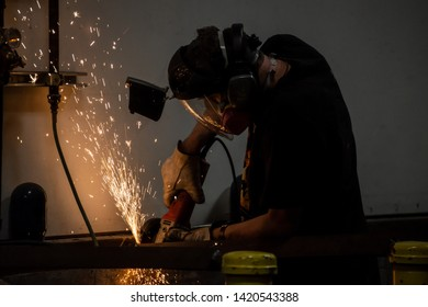 Workman grinding metal and sparks flying in the air.