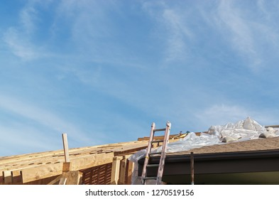 Workman ladder resting on buliding renovation. Blue sky, wispy clouds. Room for text.