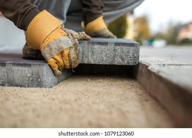 Workman laying exterior paving stones in a low angle view of his gloved hands fitting a brick into a tight fitting space on a sand foundation.