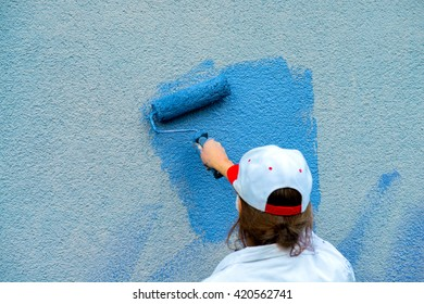 workman painting the wall with paint roller in blue