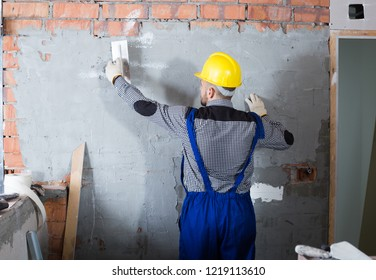 Workman is plastering the wall at the place.