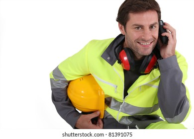 Workman in protective gear with mobile phone