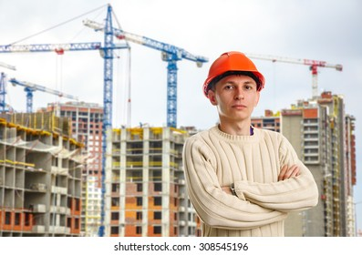 Workman in red helmet on background of buildings under construction and cranes