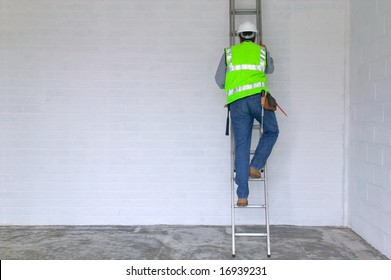 Workman in reflective vest and hard hat climbing a ladder, slight motion blur on the man.