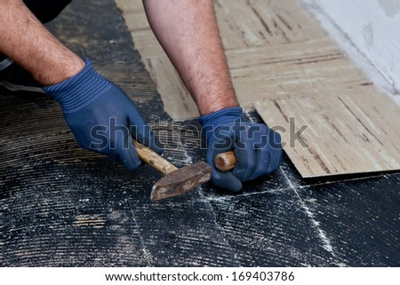 Workman removing old floor tiles using a hammer and chisel during building renovations so that he can install new flooring, close up view of his gloved hands