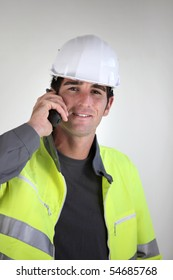 Workman with safety helmet phoning