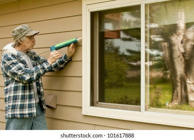 workman sealing an exterior window with caulk to reduce air infiltration