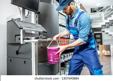 Workman in uniform putting bucket with paint into the machine for coloring in the building shop