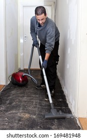 Workman vacuuming a passage during renovations after removing the old floor tiles