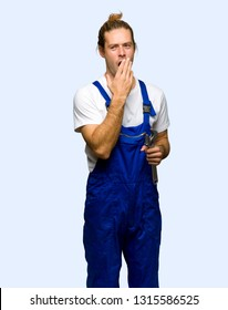 Workman yawning and covering wide open mouth with hand on isolated background