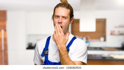 Workman yawning and covering wide open mouth with hand in a house