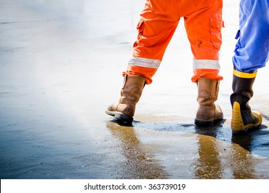 Workmans boots in oil and gas industrial, safety boos for firefighter worker petroleum process, Worker walk with safety shoes on wet floor.