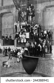 Workmen pose for a group portrait on the giant turbine in the powerhouse of the Bonneville Dam. Ca. 1937.