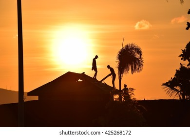 Workmen trying to finish before the sunsets near the waterfront, downtown Kingston, Jamaica.