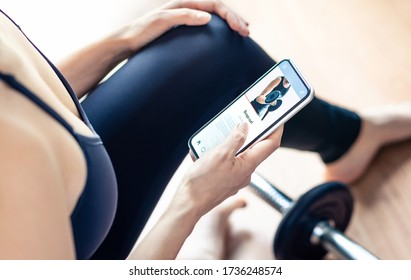 Workout app in mobile phone. Fit woman home training. Gym motivation from online personal trainer. Person watching tutorial video with smartphone. Muscle exercise with fitness coach. Sport routine.