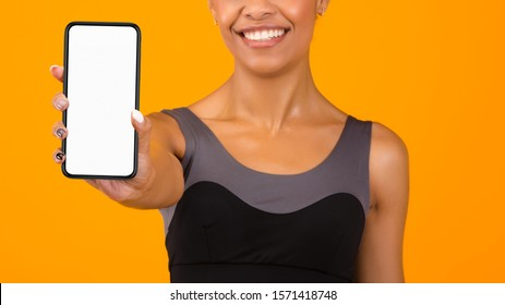 Workout App. Sporty Afro Woman Showing Smartphone With Empty Screen Over Yellow Studio Background. Panorama, Cropped, Mockup