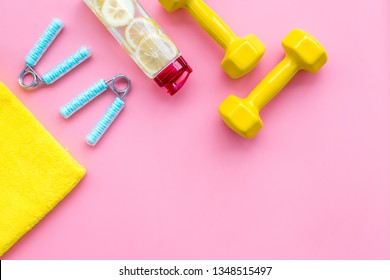 workout with bars, bottle of water and wrist builder pink background top view mockup