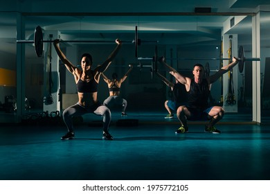 A workout couple training in the gym and doing overhead squat exercise with weight on the barbell.