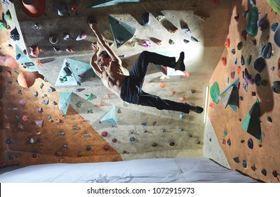 Workout exercise. top view of a man climber climbs indoors in bouldering gym. Athletic man climbing up on practice wall