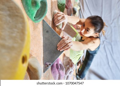Workout exercise. top view of a woman climber climbs indoors in bouldering gym. Young woman climbing up on practice wall