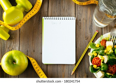 Workout and fitness dieting copy space diary. Healthy lifestyle concept. Salad, apple, dumbbell, water and measuring tape on rustic wooden table.