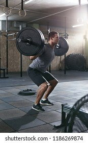 Workout At Gym. Sports Man Doing Squats With Barbell Row