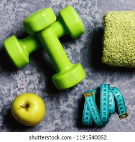 Workout and healthy lifestyle concept. Dumbbells in green color, apple, towel and cyan measuring tape on grey texture background. Sports and healthy training idea. Tape measure and fruit near barbell
