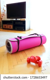 Workout in home with equipment - mat for exercises and red dumbbells on wooden floor. In blurred background television