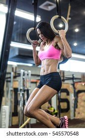 Workout on crossfit rings. Fitness woman workout on the TRX in the gym. Fitness woman workout on the CrossFit. Fitness woman in the gym. Crossfit woman. Crossfit style. Training TRX straps. TRX gym