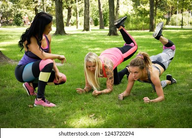 Workout at the park outdoors, two girl with their coach doing exercises on the grass.