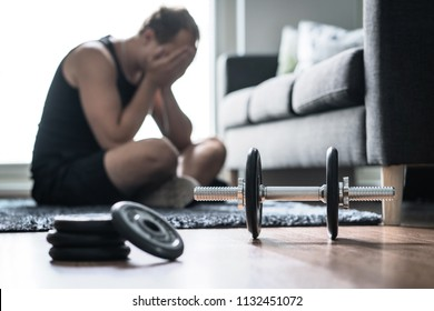 Workout problem, stress in fitness or too much training. Sad or tired man having trouble with overtraining. Exhausted and unhappy athlete with depression.