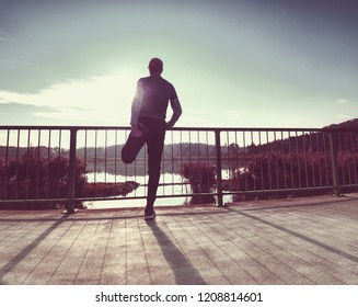 Workout runner. Man do stretching, taking a break from run outside in beautiful seaside. Fit young caucausian athletic model training for marathon outdoors